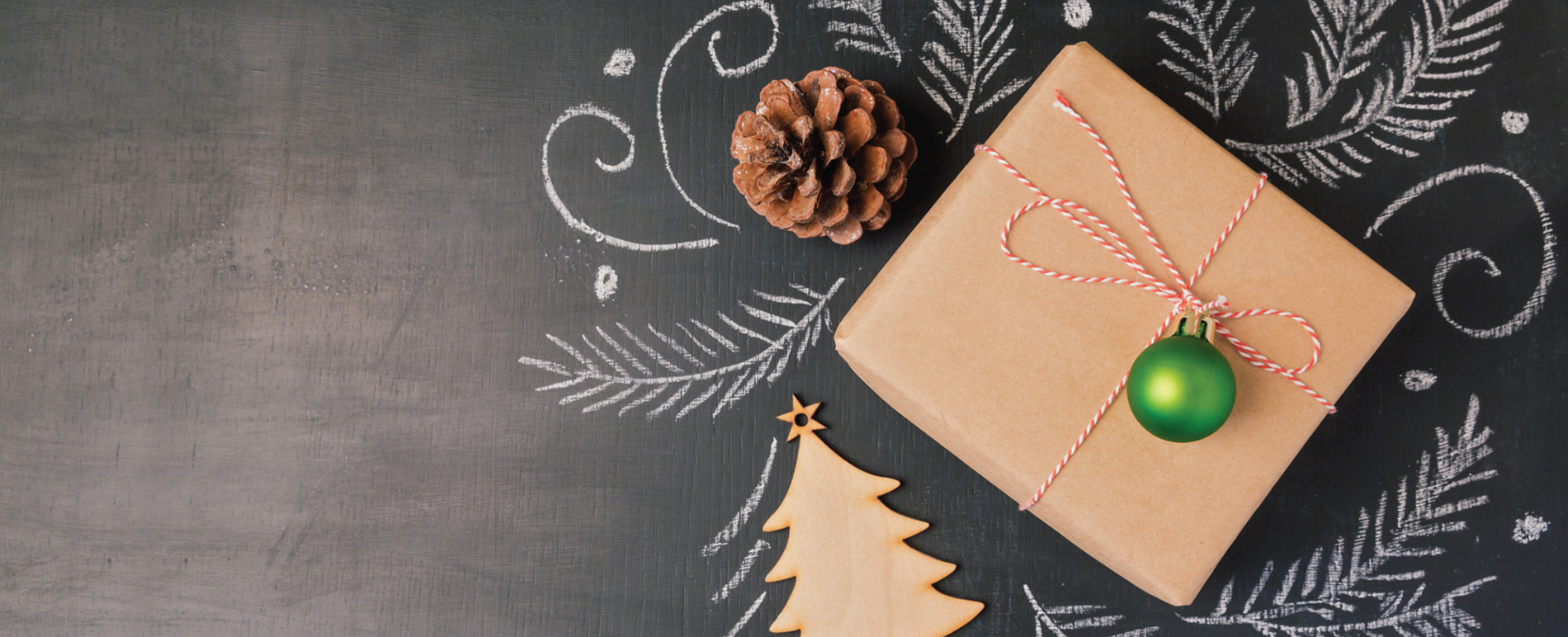 gift, Christmas cookie, pine cone and chalk designs laid out on a chalkboard
