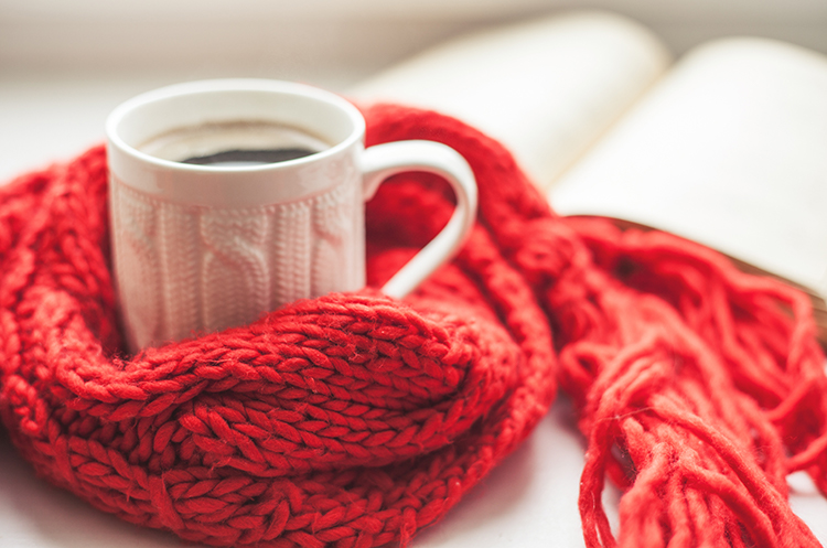 red scarf wrapped around a cup of coffee